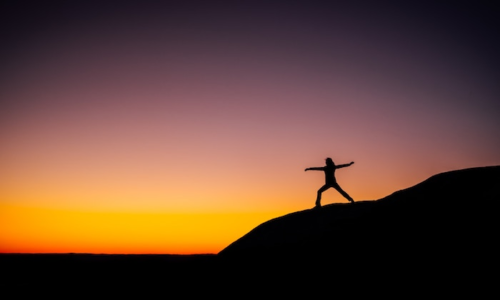 Woman stretching in the sunset on a hill
