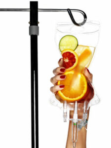 Woman's hand holding Iv with fruits and juice inside.