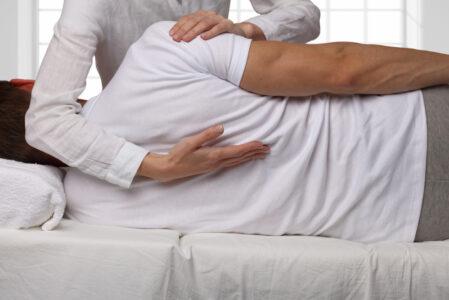 Woman readjusting a man's back